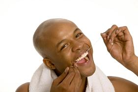 A man flossing his teeth happily.