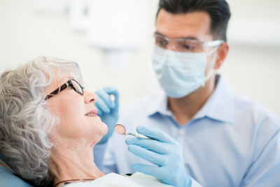 An elderly woman about to receive a root canal from her dentist.